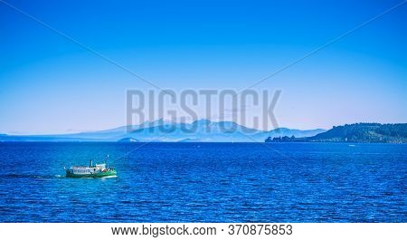 Tourist Steamboat Crossing The Deep Blue Waters Of Lake Taupo With Ruapehu Mountains In The Backgrou