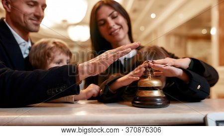Happy Family Checking In Hotel At Reception Desk. A Son And A Daughter Are Ringing A Service Bell To