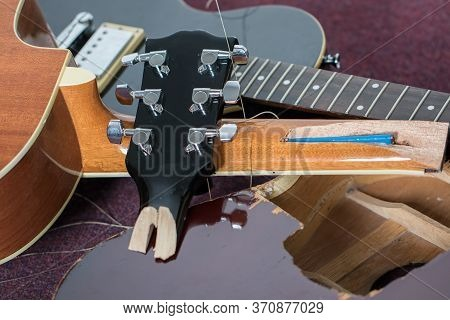 Smashed Guitars. Pile Of Broken Electric And Acoustic Guitar Bits. Close-up Of Damaged Musical Instr