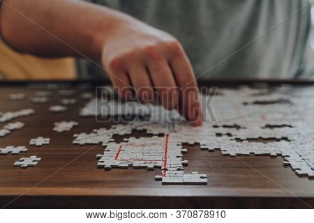 Close Up Of An Incomplete Puzzle On A Table, Male Hand Placing A Piece On The Background, Selective