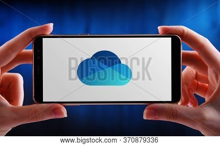 Poznan, Pol - May 21, 2020: Hands Holding Smartphone Displaying Logo Of Microsoft Onedrive, A File H