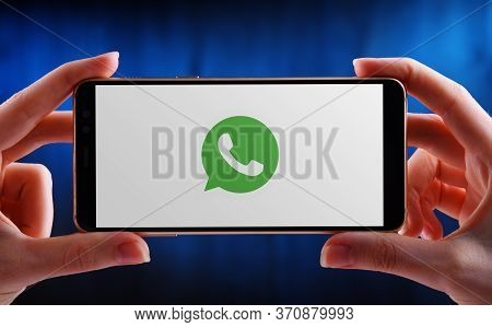 Hands Holding Smartphone Displaying Logo Of Whatsapp Messenger