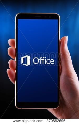 Hands Holding Smartphone Displaying Logo Of Microsoft Office