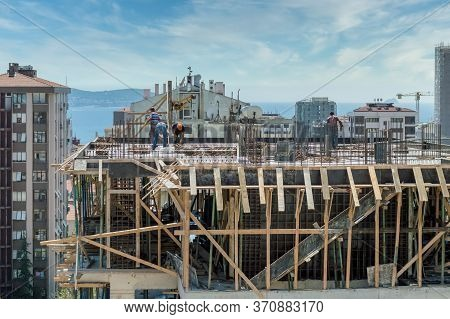 Construction Site Workers Without Protective Wear Working On The Top Of A Building Under Constructio