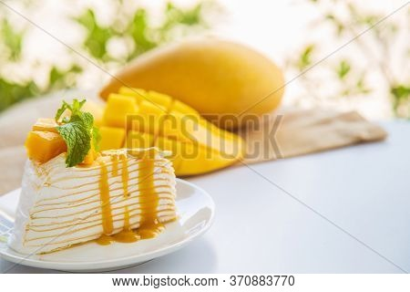 Close Up Mango Crepe Cake Sliced On A White Plate Decorated With A Piece Of Mango Fruits And Pepperm