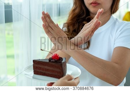 Beautiful Young Women Care For Their Health And Shape, Refusing To Chocolate Cake. Reduce Foods That