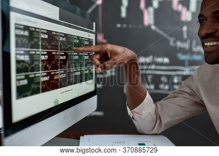 African Businessman, Trader Sitting In Front Of Computer Screen And Looking At Graph Chart With A Sm