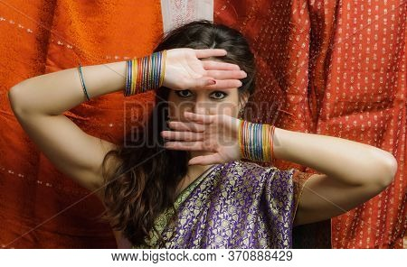 Young Woman In Indian Sari And Colorful Bangles Looking Through The Palms. Indian Style.