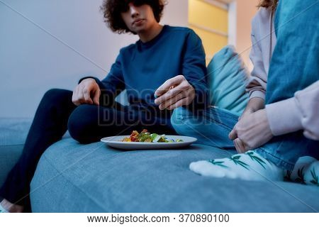 Eating Some Sweets. Couple Sitting On The Sofa In The Living Room And Eating Colorful Fruity Gummy B
