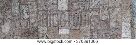 Panorama Of A Decrepit Stone Wall. A Wall Made Of Gray Rolled Vertically Laid. Vintage Background.