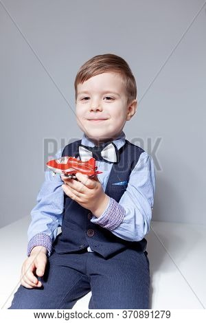 A Boy In A Shirt, Bow Tie, Vest And Trousers On A White Background Is Holding A Toy Airplane. Stylis