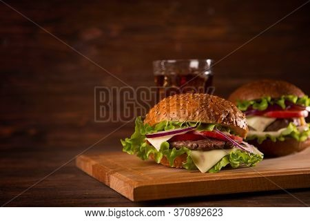 Two Hamburgers And Cola On The Table Over Dark Background