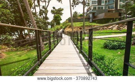 Wooden Walkway With Balustrade For Balance In The Front Yard And With Flowers And Large Trees Provid