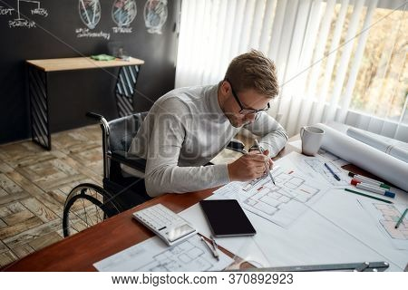 Professional Male Engineer In A Wheelchair Making Measurements On A Blueprint While Working On Const