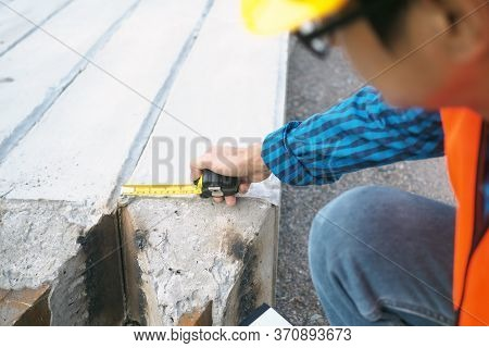 The Chief Contractor Uses A Meter Tape To Check The Size Of The Stake.