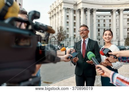 Horizontal Shot Of Cheerful Politician And His Assistant Giving Interview To Journalists. People Mak
