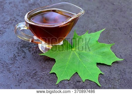 Maple Syrup In A Sauceboat And Maple Leaf On A Black Background.