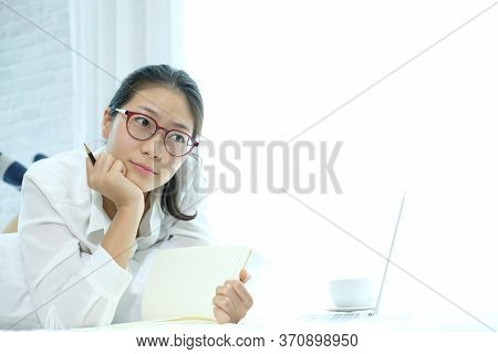 Woman Writing Note Working With Computer Laptop On Bed. Student Listen Lecture Learning Studying Onl