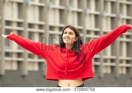 Surprised Woman In Bewilderment Looks Up Holding Hands Up