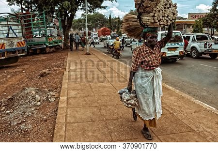 Kampala,uganda - April 11,2017:entebbe Road An Old,poor Woman Was Transporting Wood And Food By Feet
