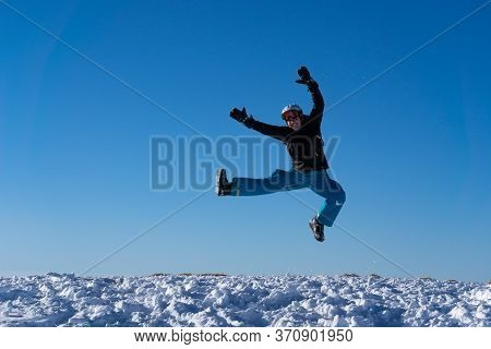 Girl With Goggles And Helmet Is Leaping Midair In Winter. Blue Sky And Bright Sunshine On The Top Of