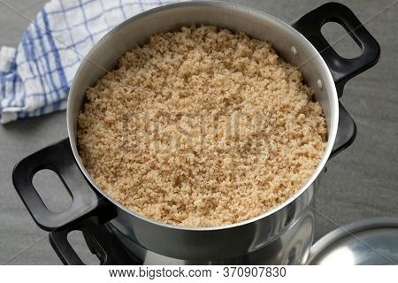 Steamed barley grits, belboula, in a traditional aluminum food steamer close up