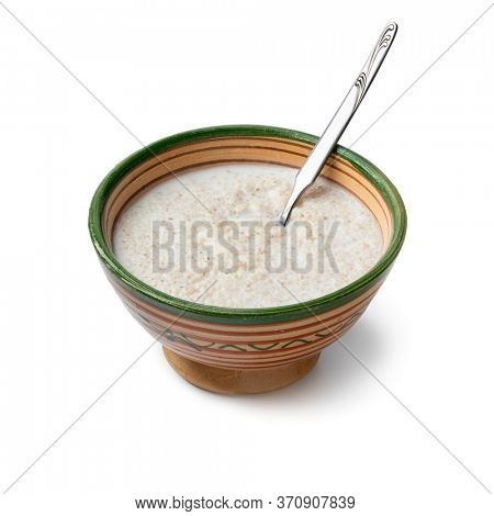 Traditional ceramic bowl with Moroccan belboula saikouk, barley grits, isolated on white background