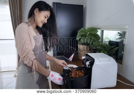 Asian Girl Use Air Fryer Machine For Cook A Chicken , This Photo Can Use For Diet Food, Oil Less, Co