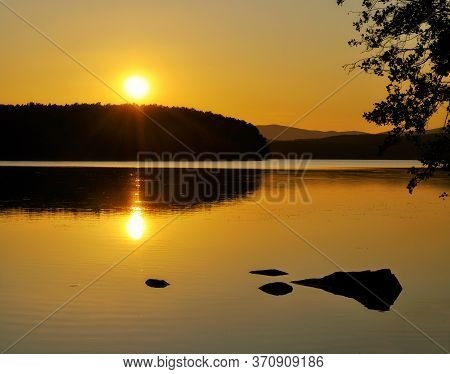 Summer sunset lake landscape - sunset on the Spruce Lake in Southern Urals, Russia. Summer water lake scene, lake summer background. Lake water in sunset, summer lake landscape