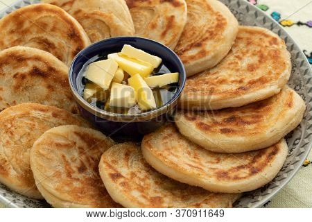 Fresh baked meloui, Moroccan pancakes with butter and honey on a plate close up