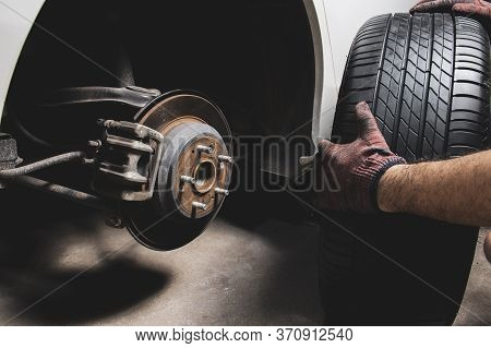 The Mechanic's Hand Holding Black Tires For Changing Alloy Wheel Into The Wheel Hub At Car Tire Shop
