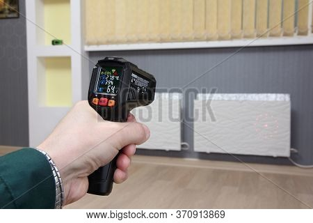 Infrared Thermometer In Hand Measures The Temperature Of Heating Radiators In A Room