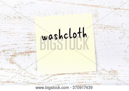 Concept Of Reminder About Washcloth. Yellow Sticky Sheet Of Paper On Wooden Wall With Inscription