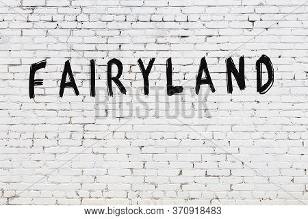 White Brick Wall With Inscription Fairyland Handwritten With Black Paint