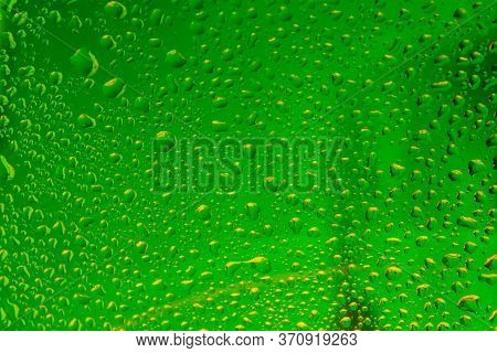 Raindrops On The Surface Of Window Panes. Natural Pattern Of Raindrops, With Green Highlights On A B