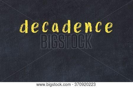 Chalk Handwritten Inscription Decadence On Black Desk