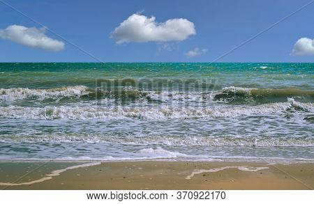 A Narrow Strip Of Sand, Foam From The Wave, Greenish Water And A Blue Sky With White Clouds Are In T