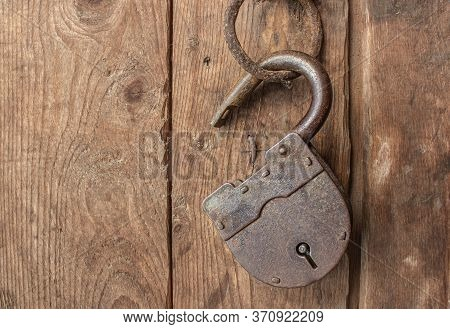 An Old, Rusty Lock Hangs Open And Without Keys On A Door Hinge. , The Concept Of Obsolete Secrets An