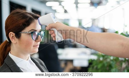 Temperature Measurement By Electronic Infrared Thermometer For Office Staff. Sick Woman In A Suit. C
