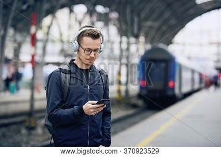Young Man With Headphones Listening Music Using Phone Against Train At Railroad Station.