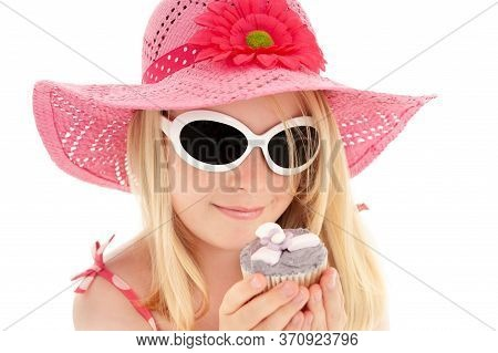 Beautiful Young Blonde Girl In Big Pink Floppy Hat And White Framed Sun Glasses Looking At A Cup Cak