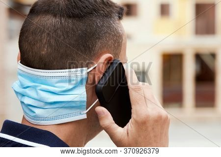 closeup of a young man on the street, in casual wear, talking on his smartphone and wearing his surgical mask in the back of his neck while is not wearing it in his face