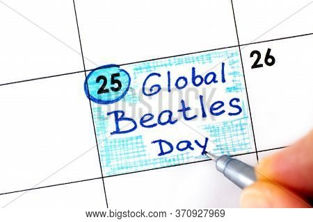 Woman Fingers With Pen Writing Reminder Global Beatles Day In Calendar. June 25.