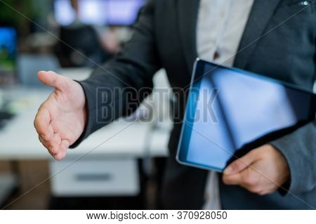 Business Woman In A Jacket And White Shirt Holding Out A Hand For A Greeting. A Faceless Business Wo