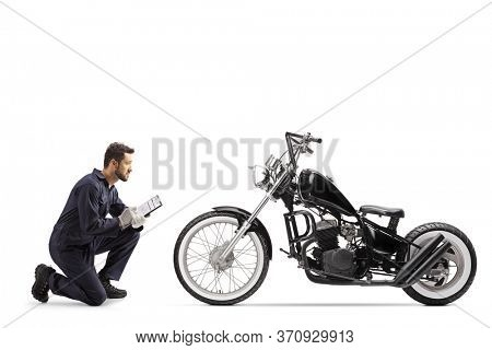 Motorbike mechanic in a uniform kneeling and looking at a chopper and writing a document isolated on white background