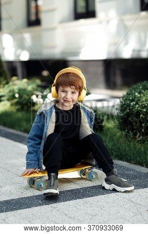 Photo Of Cute Little Boy Sitting On The Skateboard Or Pennyboard Listening Music In Headphones In St