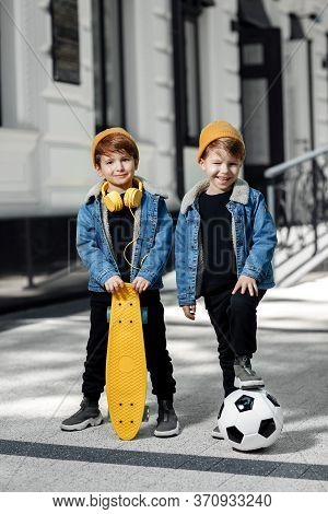 Two Cheerful Twin Boys Posing With Happy Faces In The Street. Skateboard Or Pennyboard And Soccer Ba