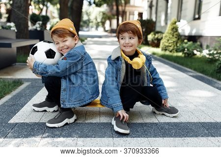Two Positive Twin Boys Sitting On The Skateboard Or Pennyboard Looking Each Over Up In The Street.