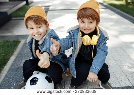 Two Positive Twin Boys Sitting On The Skateboard Or Pennyboard Showing Thumbs Up In The Street.