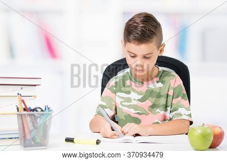 Teenager Sitting At The Desk With Homework. Back To School And Homeschooling Concept